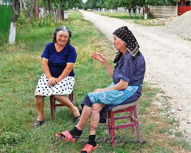 Two women chatting in front of their gate, Munteni, Romania.