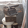 Typewriter, probably from the 50's to 70's, sitting on a toilet.