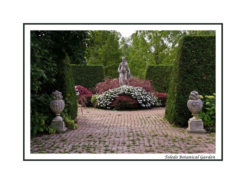 Framed version:  Garden crossroads.<br /> This statue stands at the center of a formal area that connects the Color, Grasses, and Perennial Borders gardens.  The fourth portal  (opposite the one seen in the foreground) leads to the open area that includes the Grand Allees.  I was standing in the Perennial Borders garden, looking south, when I took this.<br /> <br /> This year's color scheme for the plants in this area was very pleasing in the way it coordinated with the soft mauve colors in the bricks and the deep greens of the enclosing hedges.<br /> .<br /> Toledo Botanical Garden, Ohio.<br /> September 7, 2012.