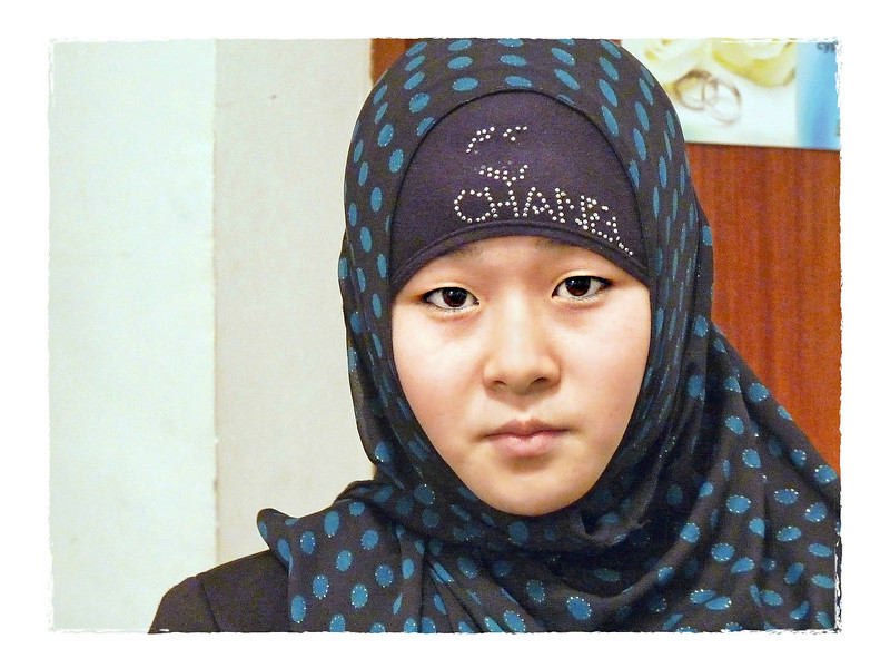 Kyrgyz girl wearing Chanel. (11.9.2011)<br /> <br /> O.K., Chanel counterfeits are everywhere in this part of the world, but, in fact there's a sad story which accounts for this girl's solemn look. Fifteen year old Rakhat has been forbidden to attend school for her refusal to remove her hijab. It is not traditional dress for Kyrgyzstan and, like many countries, they're concerned with the rising spread is Islam.