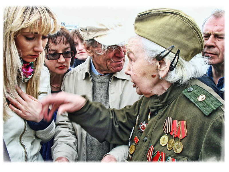 """Listening to war time stories. (5.9.2012)<br /> <br /> This woman actually helped take the Reichstag - she had the photos to prove it. In a country where almost every family lost someone during the war, young & old turn out on this day to pay their respects & listen to Veterans' stories. It's 67 years ago & seems like ancient history to [American] youth, but here it's still fresh in the minds of all.<br /> <br /> We're heading out to the celebration though it's a cold, raw & gloomy day. Thanks for all your comments yesterday. The story of October '93 is a long one. Perhaps I'll put it to paper one day. <br /> <br /> I do have a short video compilation of some the the events of the day on our site [including Rustem seconds after being shot], though much of it is raw footage & Russian TV reports, which can be found here:<br /> <br /> <a href=""""http://www.rusuphotography.com/Us/October-1993-Moscow/9239545_3m3bsg#!i=633391280&k=5WnEy"""">http://www.rusuphotography.com/Us/October-1993-Moscow/9239545_3m3bsg#!i=633391280&k=5WnEy</a><br /> <br /> I also found an interview with him from 2007 in English:<br /> <br /> <a href=""""http://rt.com/news/interview-with-rustem-safronov/"""">http://rt.com/news/interview-with-rustem-safronov/</a><br /> <br /> Will catch up with everyone this evening. Have a good day!"""