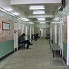 "Russian indignities. <br /> <br /> I sneaked my point & shoot into the hospital I just visited for a consultation. This is the corridor outside the traumatologist's office. The gurneys in the rear look like chain link fencing on wheels with a thin, 1/4"" pad on them as a mattress. By western standards, the place is filthy & most of the people are rude. Couldn't get a shot off in the reception area which looks more like a prison than a hospital. Built in 1763 by decree of Catherine the Great as a hospital for the poor, this isn't nearly as bad as most hospitals in Russia.<br /> <br /> I'd have avoided it like the plague except that one of the only hand specialists in the entire country is here. For 3 months I've had a problem with my thumb & since we returned from our holidays it suddenly locked in position. I'd been to every specialist imaginable most of whom diagnosed it as arthritis (though all my other fingers are fine). When I asked the orthopedist if would always be this way he answered, ""God knows"". Finally, one of my doctors ordered an x-ray. The x-ray technician looked at my thumb (before taking the x-ray) and said, ""It's arthritis - what, you don't understand/can't accept that you're an old lady & that's just how life is!""<br /> <br /> To set the record straight - yes, I am over 50, but I didn't quite think I was ready for the graveyard yet. I was so outraged that I went to the head of the clinic who, to make a long story short, gave me a referral to this hospital.<br /> <br /> Thankfully, the doctor I saw was nice & knowledgeable. She could only smile sardonically when told of the arthritis diagnosis. Seems there are tears in the tendon that enable the thumb to move. I need to have an ultra-sound next week to confirm (this lovely facility doesn't have one), but because nothing was done 3 months ago when the problem appeared, I'm told there's a 99.9% chance I'll need surgery. No details about that thus far.<br /> <br /> Nothing special about this photo - just a slice of Russian reality. Thanks for letting me sound off. (Feb. 3, 2011)<br /> <br /> 2.28.2011 Update: So far I'm in a cast. Another ultrasound next week should tell whether or not I need surgery."