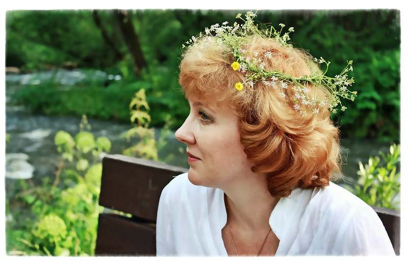 Strawberry blonde with flower wreath. (7.11.2012)<br /> <br /> We took a break from the conference & sat by the river with this woman from Khakassia's Ministry of Culture, the organizers of the event. While we sat, she made this wreath following an ancient Slavic pagan tradition in honor of Ivan Kupala Day. According to Wikipedia, girls float wreaths of flowers on rivers in an attempt to gain foresight into their relationship fortunes from the flow patterns of the flowers on the river. Hers went in the river shortly after this shot. <br /> <br /> Thanks for your comments on yesterday's shot of Salome. Based on my last two Dailies, I'd say character trumps beauty :)<br /> <br /> I've got a busy day & a touch of dysentery, so will catch up this evening.