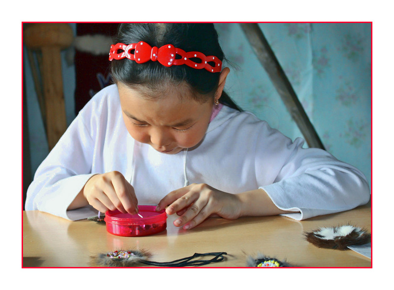 Red headband. Evenk girl concentrating on her bead work while making traditional Evenk amulets. <br /> <br /> Off early today so am posting even before the new Smug day begins. Going to see another specialist hoping for some answers. Have a good day. (5.5.2011)