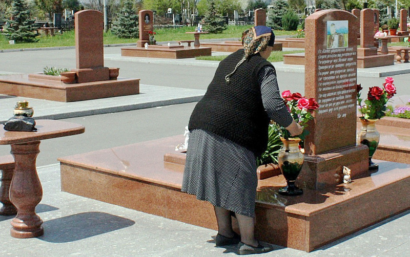 Grandmother arranging flowers in Beslan's City of Angels Cemetery. <br /> <br /> On the 1st day of school, September 1, 2004, terrorists took over a school in Beslan & held more than 1,000 people including 777 children hostage for 3 days. 334 hostages, many of them children, lost their lives. This cemetery was built for the victims. (6.4.2011)