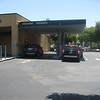 July 10... cars are waiting in the hot sun for the two drive thru ATMs.. .next to them are 4 completely empty walk-up ATMs.