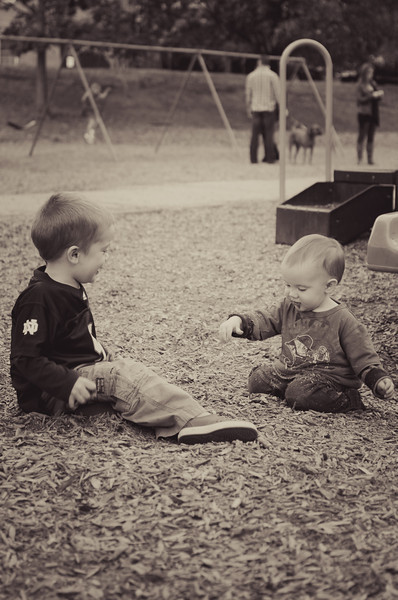 Yes, the wee one is eating, or attempting to eat, the playground wood chips that his brother is depositing on his lap.