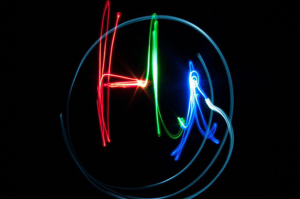 "Day 8:  Light drawing.  Ok, I have to admit that the first time I tried this I forgot that it would show up backwards to the camera so i spelled ""iH.""  Not a bad redo though.<br /> How this was done:  Setup the camera on a tripod with a remote trigger.  Turn off shake reduction (very important when a camera is mounted on a tripod.  It will look for shake and if there is none, it actually introduces some).  Set the camera to shutter priority and set it to 10-20 second exposure.  Manually focus with the lights on.  Turn off lights.  Grab an LED flashlight that you can change colors with (turn it on before pressing shutter button).  Press shutter on remote and then just paint.  You don't have to go slow, just sort of a medium speed until the shutter clicks shut.  You can see in the ""H"" where i had to pause to switch to green."