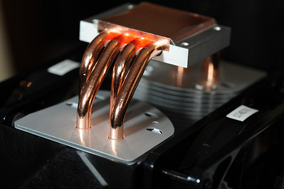This is the CPU cooler, shown upside down. The copper plate at the top will be pressed directly against the CPU. The copper plate will quickly move heat through the tubes and into the fins, through which fans will blow air. This will provide highly effective heat dissipation, assuming that the contact between the copper plate and CPU is perfect. Without a cooling mechanism in place, most CPUs will overheat and die within 10 seconds of power-on.
