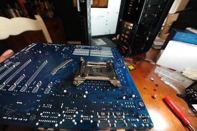 The cooler attaches to the plate on the underside of the motherboard. Tighten it down.