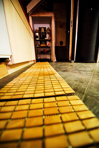 Tile-looking mats atop tiles in the kitchen provide a place for things to crash from the counter without damaging the floor.