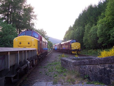37406 stands at Upper Tyndrum with a Millerhill - Rannoch ballast as 37405 arrives with the Fort William - London Euston Caledonian Sleeper. 07/06/06. Published in West Highland News Summer 2008.