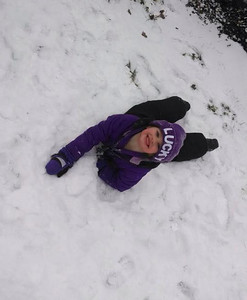 Alysa, 4, is all smiles after jumping into the snow.