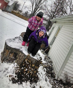 Alysa, 4, prepares to jump from a tree stump as her sister Kyrah, 6, looks on.