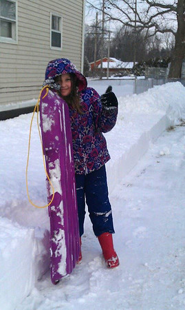 Keira Franklin, 8, of Elyria is excited to go sledding on the snow day Feb. 18 after helping shovel the driveway on Sandalwood.