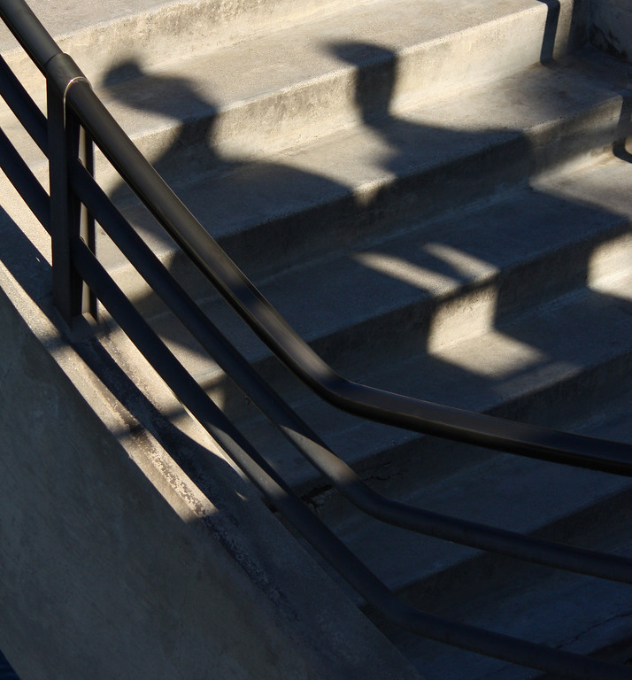 Shadow of Two People Climbing Stairs