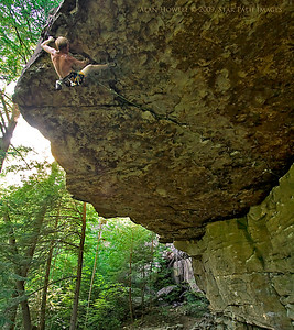 The baddest roof in the SE! Aaron on the finishing holds of Maximum Overdrive, 5.13b/c, in 92 degree temps at the Steven King Library.