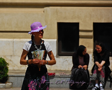 Woman with pink hat and hand fan, Antim Ivireanu Monastery, Romania.