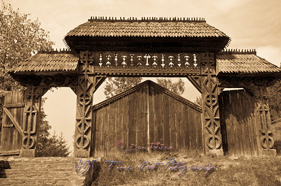 Traditional carved wooden gate from Maramures region, Romania, sepia tones.