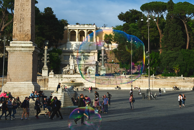 Giant soap bubbles on Piazza del Popolo, Rome. Pincio and Villa Borghese in the background.