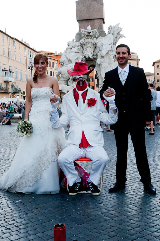 A bride and groom with a street mime in front of the Fountain of the Four Rivers, Piazza Navona