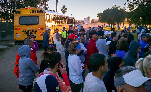 The sun rises as runners wait in line for the porta-potties.  The queue periodically has to bunch up as shuttle busses come and go.