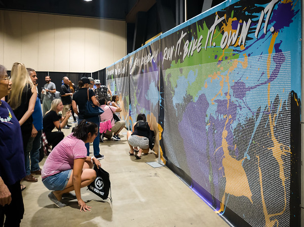 Participants in this weekend's events try to find their name on the wall