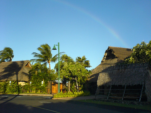 A rainbow is clearly visible as the sun begins to touch the site of the Old Lahaina Luau
