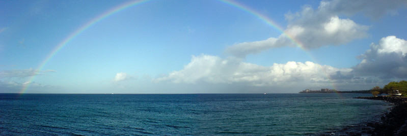 Both ends of the rainbow appear to end upon the water near Ka'anapali