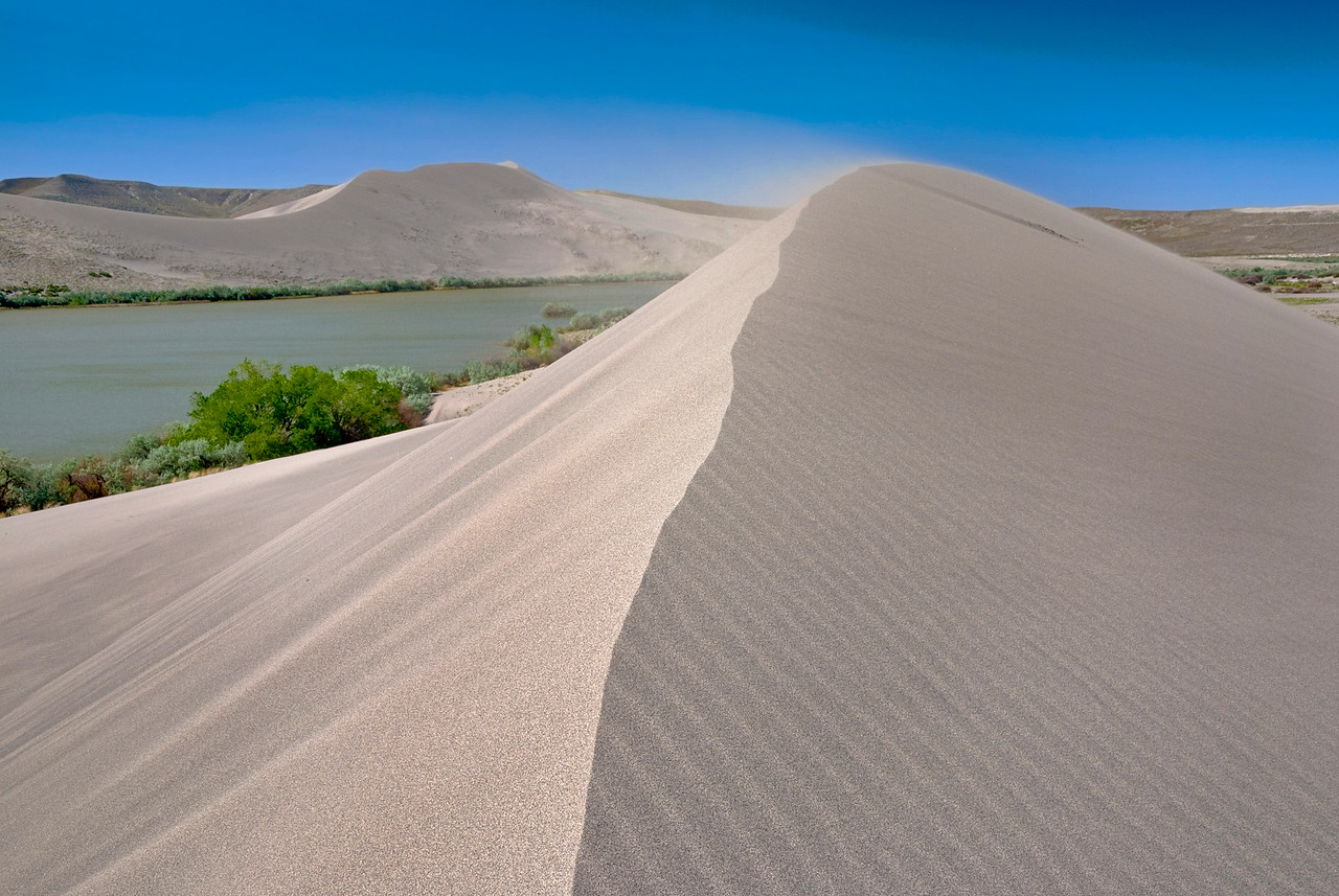 Natural Sand dune has wind blowing sand from the top