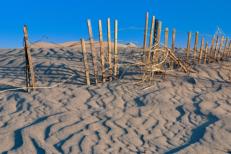 Wind blown sand has buried an old wooden fence