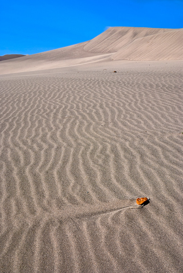 The wind has blown ripples in the sand around a rock