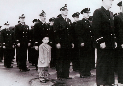 """Looking up at this photo on his office wall, CFD First District Chief Bob Hoff said; """"I look at that every day, and it continues to drive me, to serve as my motivation to be the best I can be…. Every day.""""  Photo: Little Bob Hoff at five years old with his Dad, Chicago Firefighter Captain Thomas A. Hoff at an inspection in Soldier Field in 1960. Captain Hoff was killed when a building collapsed over him during a fire at 70th and Dorchester in Chicago, Feb 14, 1962. The story of Thomas Hoff, Bob, and his older brother fireman, Ray, served as the basis for the Film """"Backdraft"""".  An SS1 member (see 1st photo in this exhibition entitled SS1), Chief Hoff has been concerned with firefighter safety and survival his entire career co-authoring a book """"Firefighter Safety and Survival with Lt. Rick Kolomay, another fireman's son. *  *Hoff, R., Kolomay, R. (2002). Firefighter Safety and Survival, Penwell Publishing."""