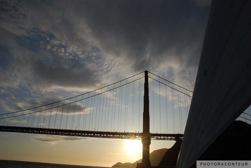 """Through the Sails II"" ~ Fluffy clouds fill the sky as the sun sets beyond a windblown sail and the Golden Gate Bridge."