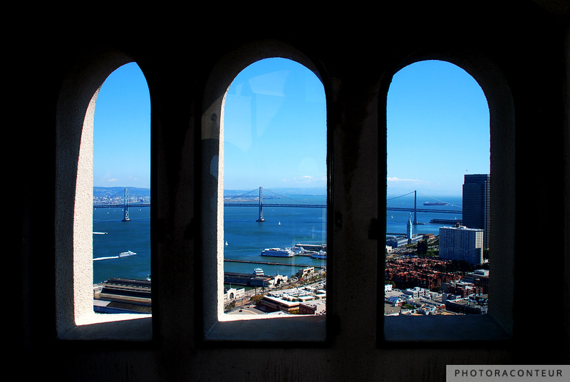 """Bay Bridge Through the Windows"" ~ From atop Telegraph Hill, the Bay Bridge appears through the arched windows of Coit Tower.  The Old Ferry Building and several piers can also be seen as boats and cargo ships traverse the San Francisco Bay."