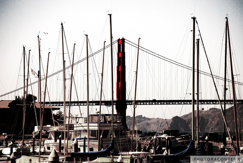 """Furled Sails"" ~ The Golden Gate Bridge meshes perfectly into a landscape filled with docked sailboats and their furled sails.  A vintage treatment has been applied to the photograph to focus the eye on the homology of shapes and patterns in the scene while at the same time accentuating the color of the bridge tower."