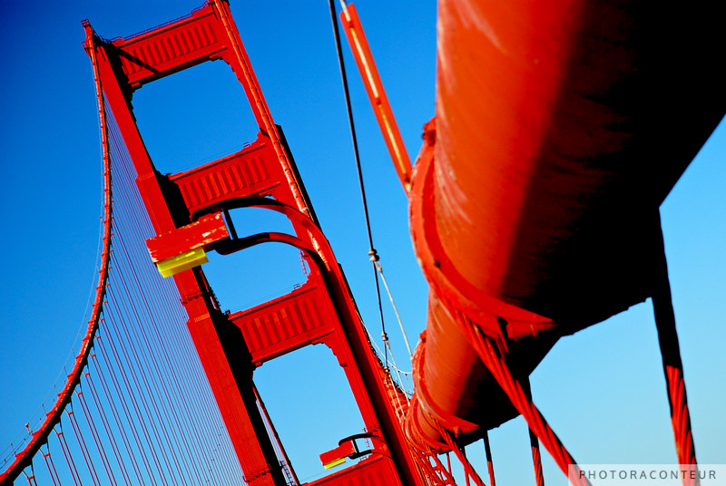 """Golden Gate Suspension"" ~ The two cables that gracefully suspend the bridge deck are 36.5 inches in diameter and measure 7,650 feet long between anchorages.  Each cable weighs 11,000 tons.  Notice the yellow light lenses.  When the original 1937 fixtures were modernized in 1972, these lenses were designed to mimic the yellow glow of the old lamps."