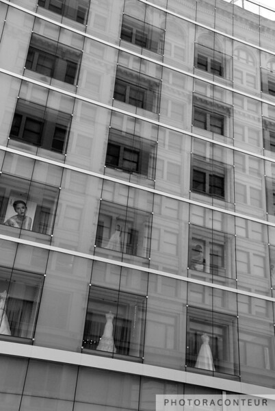 """""""Window Shopping"""" ~ Wedding dresses are uniquely displayed in the windows of a bridal shop in Union Square. The building recently underwent acomplete renovation that artfully preserved the original1907 brick exterior by encapsulating it behind layers of translucent and frosted glass. The building stands in striking contrastamongst the dark masonry buildings thatsurround it. The reflection of a 12-story building completed in 1909 appears in the glassfaçade, presenting a distinct example ofharmoniously blending modern architectural elements into San Francisco's cityscape that is filled with historic architecture."""