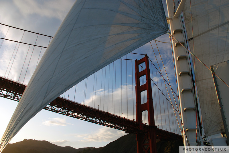 """Through the Sails"" ~ The goal of any photographer visiting an extremely popular travel destination is to try to find a unique perspective of landmarks. This is especially true for the iconic Golden Gate Bridge in San Francisco.  We've all seen dramatic photos of the bridge peaking through dense fog, or with a foreground of waves blurred by a slow shutter.  But how many shots have you seen with the bridge framed by a windblown sails?  This wasn't a planned shot at all of course, but this composition revealed itself to me just as our catamaran tour was about to pass under the bridge.  If this shot wasn't enough, I was also fortunate enough to capture ""Sunset Sailboat"" just minutes later."