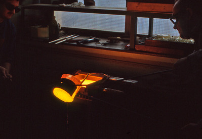 This is a shot of a Leica technician pouring the glass to make a Noctilux lens. The glass is produced in a platinum crucible that holds 1 litre of molten glass. The kiln is outside the Leica factory.