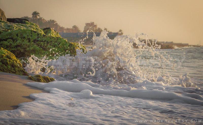 A tiny wave splashes over the beach rocks. North Sinai beach, Egypt.