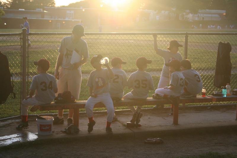 #0437 sun-hazed kids baseball team wait on the bench for their turn at bat