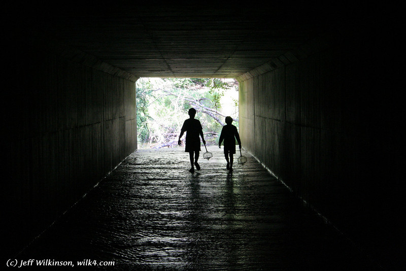 #6333 kids silhouetted against the light as they explore a stream culvert