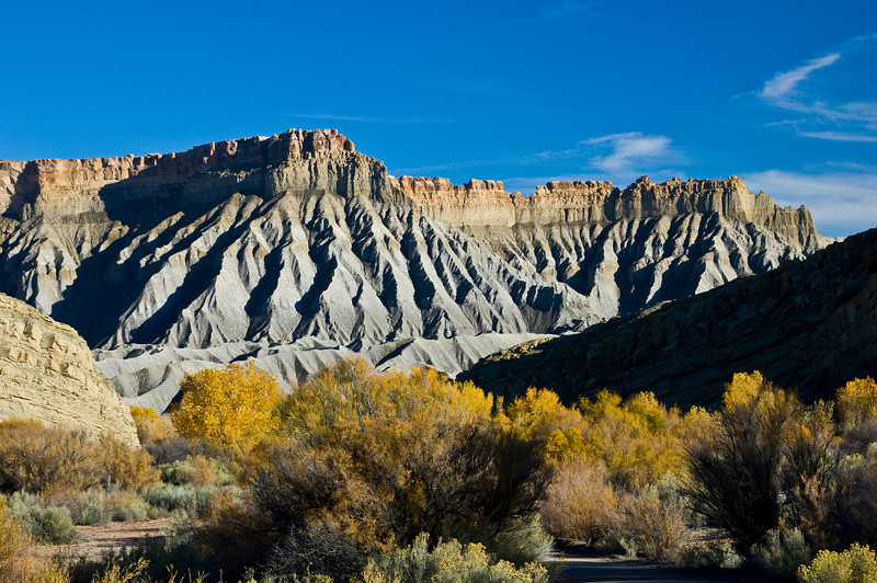 Nobody, North America, USA, Utah, Scenic Eroded Talus Slopes along Utah Highway 24 of the Upper Blue Hills, and South Caineville Mesa, Snow-capped Henry Mountains, Fall Color