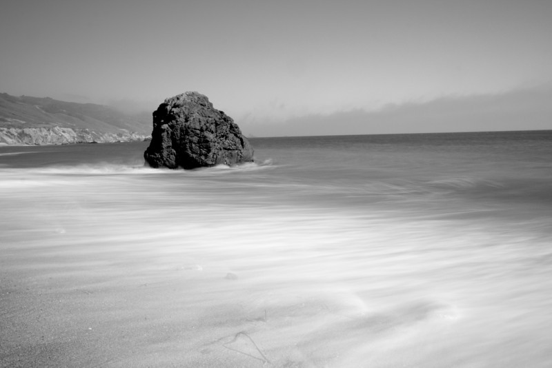 Day 9. July 17, 2010. Rock on the beach at Andrew Molera State Park. My first time using a spiffy new ND-1.8 filter, and it was quite the success. I wanted a longer exposure to get a smooth fog-like surface to the water, so I stopped down to f/16 at ISO 100 for a 1 second exposure in early evening light. I love Big Sur.<br /> <br /> 17-55mm f/2.8 IS @ 18mm. f/16. 1s. ISO 100. ND-1.8 filter.