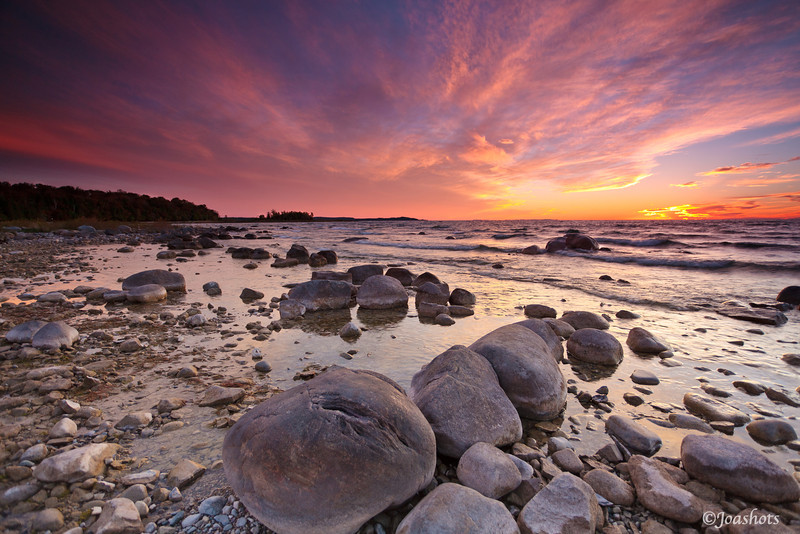 Northport, Leelanau township, MI<br /> Shoreline boulders watch in silence, as soft light bounces down from sinewy clouds minutes after sunset.