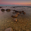 Northport, Leelanau township, MI<br /> Stepping stones: the first glimmer of dawn imparts a golden wash over a pebbled beach
