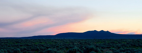 This sunset image at the Rio Grande River Gorge bridge is not of clouds, but of smoke wafting over the desert from a range fire a few miles away.  Gray and unexciting to the naked eye, this color was only visible after oversaturating the image.