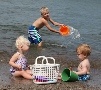 Kaylie Brown, 1, and Shane Tucker, 15 months, enjoy the beach while Shane's cousin Tyler Brown splashes in the lake in Vermilion on Labor Day. RAY RIEDEL/CHRONICLE