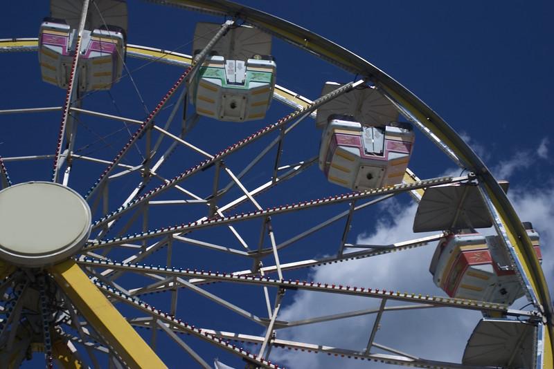 A section of a ferris wheel at a fair against a blue sky